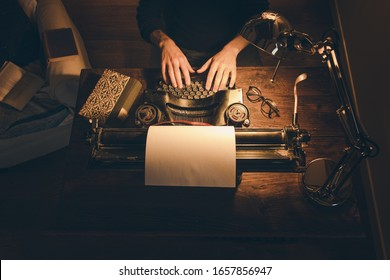 Typing hands of a writer looking for inspiration to start a new novel on his vintage typewriter in a retro style studio: a wooden desk lit by a lamp, an old book and a pair of glasses.