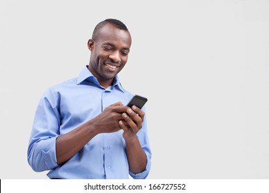 Typing a message. Cheerful black man typing something on the mobile phone and smiling while standing isolated on grey