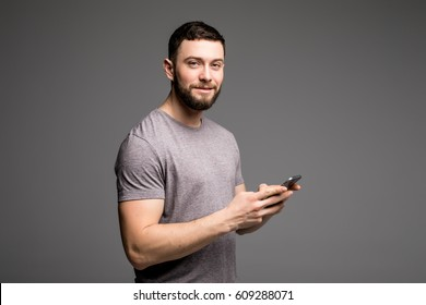 Typing message. Handsome young man in shirt holding mobile phone and looking at camera while standing against grey background