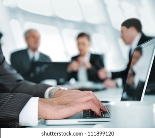 Typing on laptop while the business group having meeting