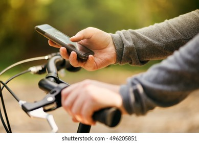 Typing text message during bicycle ride, woman with bike using mobile phone outdoors during autumn season, lifestyle and technology concept, selective focus