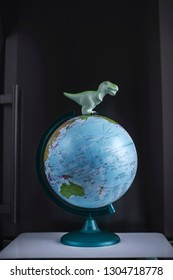 Tyrannosaurus dinosaurs toy on Globe model on dark background. Global warming and disaster concept.