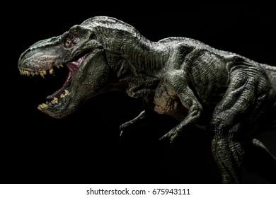tyrannosaurus toy on a dark background close up