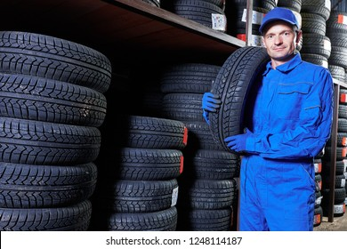 Tyre replacement. mechanic holding winter tire in store warehouse