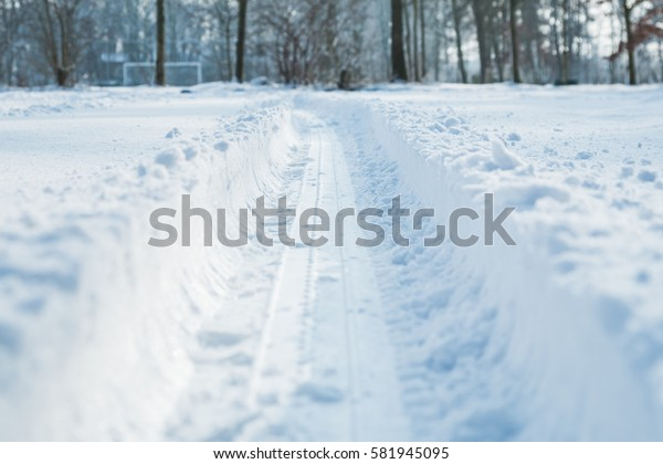 Tyre track imprinted in the snow during the winter season, low angle