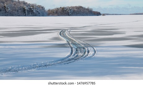 Tyre tracks in melting snow on ice on lake