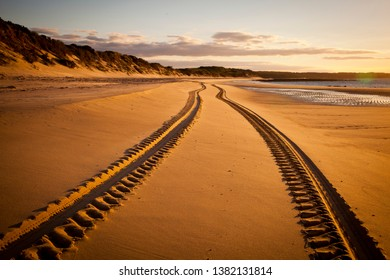 Tyre tracks on a sandy beach leading into distance during sunset.