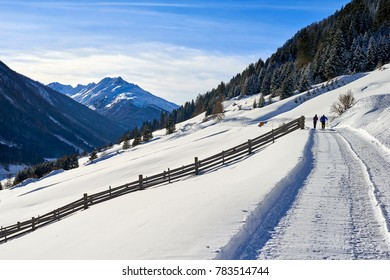 Tyrol Alps winter landscape: snow-covered countryside road on hill slope, two people are walking