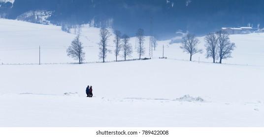 TYROL, AUSTRIA - CIRCA 2017: Two men walks in the snow at winter circa 2017 in Tyrol.