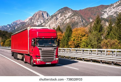 TYROL, AUSTRIA - October 14, 2017: Red truck on a high-speed mountain road. In the background are mountains and trees with red and yellow leaves.