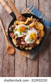 Tyrolean fried potatoes with meat, bacon and eggs in a pan. vertical top view