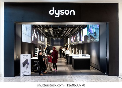 Tysons Corner, USA - January 26, 2018: Dyson vacuum cleaner store, shop, facade, storefront, door entrance with people, Muslim woman walking, standing in shopping mall in Virginia