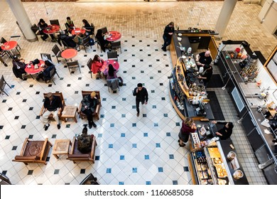 Tysons Corner, USA - January 26, 2018: High Angle view on food court, Starbuck's cafe, people sitting on chairs by tables, drinking coffee, eating in shopping mall in Virginia