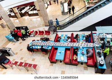 Tysons Corner, USA - January 26, 2018: Wasabi Sushi restaurant, cafe with people sitting, eating, conveyor belt bringing food, meals, dishes, plates with desserts, chopsticks