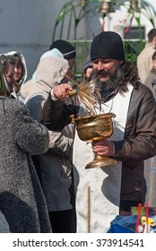 Tyumen, Russia - April 27, 2008: The orthodox priest consecrates believers and Easter cakes with the help an aspergillum. Easter