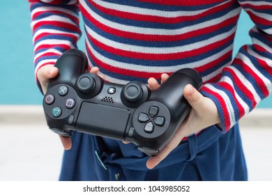 Tyumen, Russia - February 14, 2018: A little girl is holding a Sony Playstation gamepad.