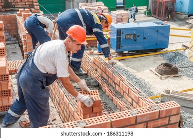 Tyumen, Russia - July 31, 2013: JSC Mostostroy-11. Construction of a 18-storeyed brick residental house at the intersection of streets of Nemtsov and Tsiolkovsky. Team of bricklayers behind work
