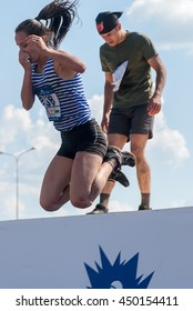 Tyumen, Russia - July 9, 2016: Steel Character extreme race on Voronino Hill. Pretty girl jumps in water
