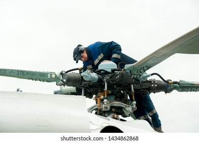 Tyumen, Russia - June 19, 2019: Aircraft repair helicopter UTair Engineering plant. Male mechanic in uniform examining helicopter. Pre flight inspection at the airport