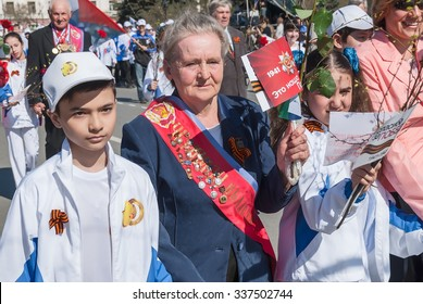 Tyumen, Russia - May 9. 2009: Parade of Victory Day in Tyumen.  Veterans of sport, honored coaches and athletes with granddaughters walking