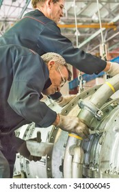 Tyumen, Russia - November 14, 2007: JSC Tyumenskie Motorostroiteli. Plant on production and repair of aviation engines. Workers install aviation engine