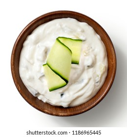 Tzatziki in brown rustic wood bowl with cucunber slice isolated on white from above.