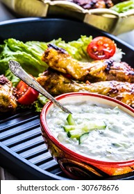 Tzatziki sauce or dressing with grilled chicken legs and fresh vegetable,lettuce salad and cherry tomatoes.
