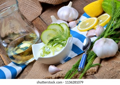 Tzatziki - traditional Greek dressing or dip sauce, garlic, lemon, dill, cucumber and jug with oil in background