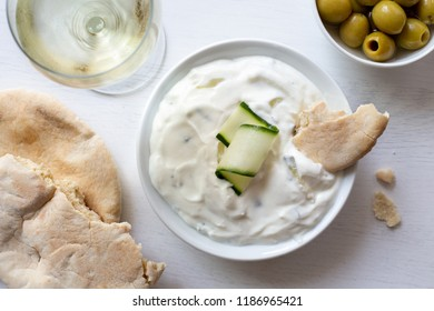 Tzatziki in white ceramic bowl with a cucumber slice and a piece of pita bread next to pita bread, olives and a glass of white wine from above.