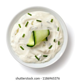 Tzatziki in white ceramic bowl isolated on white from above. Slice of cucumber and chopped chives.