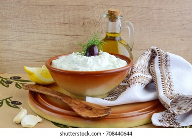 Tzatziki - yoghurt sauce with cucumber, dill, olive oil, lemon and garlic in a traditional bowl,traditional greek cuisine.Top view