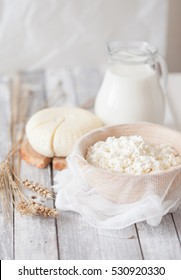 Tzfat cheese, milk, cottage cheese and wheat on old wooden background. Symbols of jewish holiday Shavuot. High key. selective focus