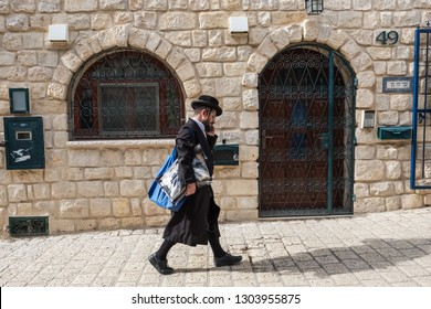 Tzfat, Israel - November 18, 2018: Orthodox jewish man walking on the street of Safed city. Tzfat has a reputation as the city of Kabbalah.