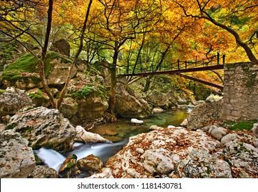 """TZOUMERKA MOUNTAINS, GREECE. Metallic bridge in the canyon of Chrousias river (also known as """"Stavraetos canyon""""), that separates Syrrako and Kalarrytes villages,  Ioannina, Epirus, Greece."""