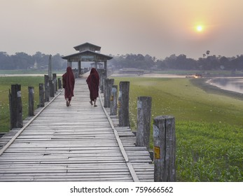 U Bein Bridge, Amarapura, Mandalay, Burma: Burmese monks walk across the U Bein Bridge above Taungthaman lake in Amarapura at sunset. U Bein Bridge is the world's longest teak bridge (1.2 km)