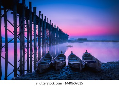 The U Bein Bridge in Mandalay, Myanmar in winter season is a old biggest wooden bridge of the world and  wooden boats with soft fog ,flock of birds at blue twilight sky background.