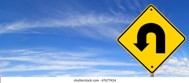 U turn road sign, against panoramic blue sky.  Time to change direction.