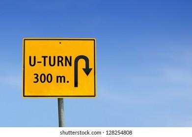 U turn road sign on sky background