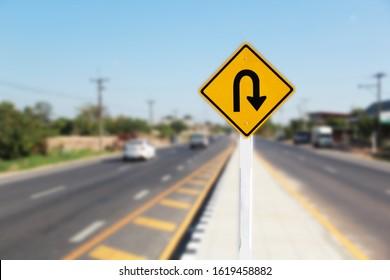 U turn sign on road blurred background