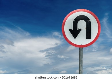 U turn sign on white cloud and blue sky background with clipping path