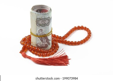 UAE dirham notes rolled with rosary