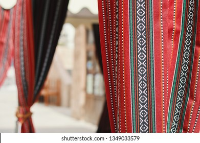 UAE, Dubai - January, 2019: Tent with curtains in traditional arabic style - handmade sadu of bright red color at Al Seef promenade