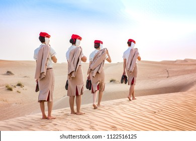 UAE, DUBAI, May 2018: four Emirates airlines cabin crew, flight attendants walking through the desert on sunset