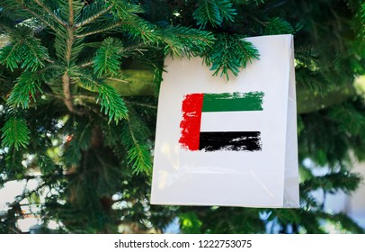 UAE flag printed on a Christmas shopping bag. Close up of a shopping bag as a decoration on a Xmas tree on a street. New Year or Christmas shopping, local market sale and deals concept.