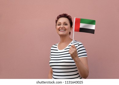 UAE flag. Woman holding the United Arab Emirates flag. Nice portrait of middle aged lady 40 50 years old with an U.A.E. national flag over pink wall background.