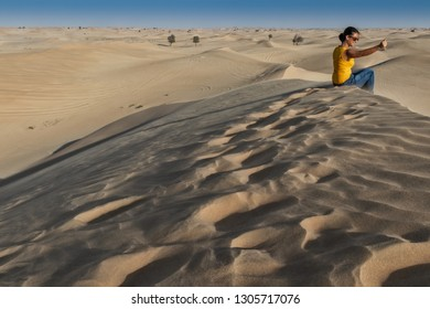 UAE/ABUDHABI - 13 DEZ 2018 - Photograph of woman sitting on top of a Dune in the desert of Abu Dhabi. UAE
