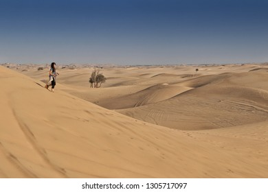 UAE/ABUDHABI - 13 DEZ 2018 - Photograph of woman on top of a dune in the desert of Abu Dhabi. UAE