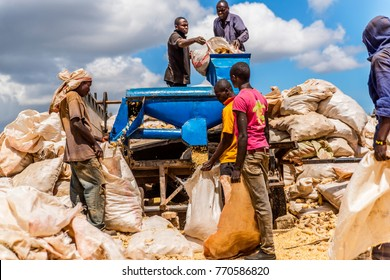 Uasin Gishu County, Kenya, Dec 6, 2017: African farm workers using tractor powered shelling machine to process dry maize husks into cobs and kernels. Cobs for furfural production. Kernels for food.