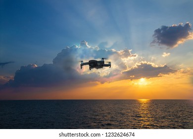 UAV drone copter flying with digital camera.Drone with high resolution digital camera. Flying camera take a photo and video.The drone with professional camera takes pictures of the sky and sea.