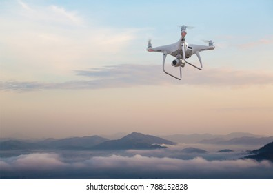 UAV drone copter flying with digital camera.Drone with high resolution digital camera. Flying camera take a photo and video.The drone with professional camera takes pictures of the misty mountains.